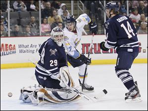 Toledo Walleye player Trevor Parkes, 27, watches as the puck gets past Greenville Road Warriors goalie Nic Riopel (29) during the first period at Huntington Center, Friday.  At right is Road Warrier Jeff Caister, 14.