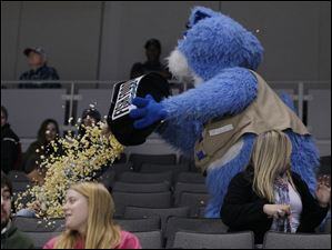 Toledo Walleye mascot Cat Trick dumps a bucket of popcorn on unsuspecting fan Brad Freyer.