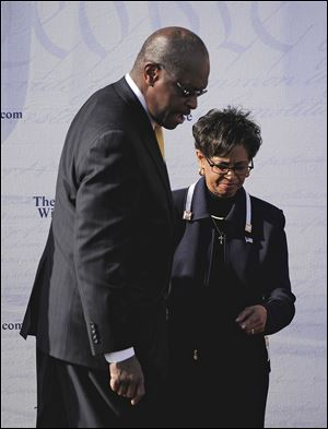 Herman Cain, left, steps off stage with his wife, Gloria, after he announced Saturday at an Atlanta rally that he was suspending his presidential campaign.