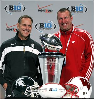 Michigan State coach Mark Dantonio, left, and Wisconsin head coach Bret Bielema pose with the Big Ten championship trophy during a news conference in Indianapolis, on Friday. Michigan State is scheduled to face Wisconsin in the Big Ten Championship game on Saturday.