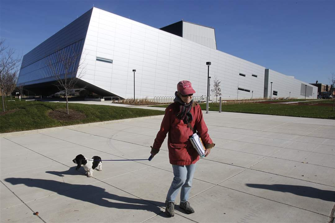 Karen-Kakas-an-art-education-instructor-walks-her-dog-past-the-new-Wolfe-Center