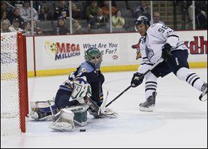 Toledo Walleye goalie Ryan Zapolski, 35, stops a shot by Chicago Express player Caz Johnson, 98, during an Express power play during the second period at the Huntington Center, Saturday.
