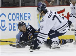 Toledo Walleye player Kyle Rogers, 17, falls down as he passes the puck past Chicago Express player Pierre-Luc Faubert, 72, during the first period at the Huntington Center, Saturday.