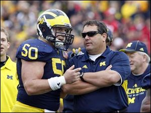 Michigan offensive lineman David Molk (50)  is a finalist for the Rimington Award while Wolverines coach Brady Hoke is a finalist for the Coach of the Year Award.