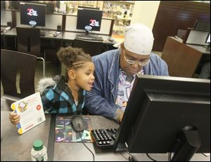 Janice Holmes uses a computer in the newly reopened Kent Branch of the Toledo-Lucas County Public Library as her 3-year-old granddaughter Surrya Silver watches. The branch is in the Old West End.