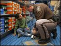 Toledoan Joshua Taylor, 5, gets his shoes fitted by Sylvania Township police officer Bill Tollison during the Shop with a Hero shopping spree at Meijer in Sylvania Township, Ohio.