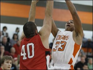 Sylvania's Nate Hall (33) is fouled by Bedford's Matthew Boehm (40).
