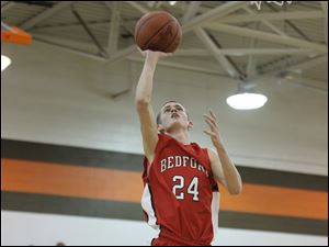 Ryan Rightnowar (24) of Bedford reaches for the hoop for two points.