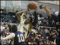 Whitmer's Leroy Alexander, 24, runs into some resistance from St. John's players Austin Gardner, 10, and Alex Carter, 4, during the game at Whitmer on Friday, Dec. 9, 2011.