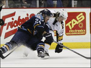 Walleye player Christopher DiDomenico (24) gets control of the puck as he battles Cyclones player Brent Clarke (25) during the second period.
