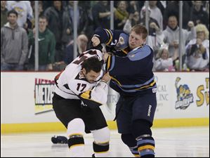 Walleye player Matt Krug (7) and Cincinnati  Cyclones player Mike Liambas (17) fight to start the third period.