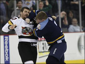 Walleye player Matt Krug (7) and Cincinnati Cyclones player Mike Liambas (17) continue to fight.