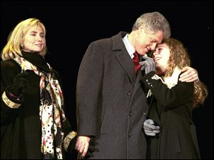 Chelsea Clinton gets a hug from her father, the President-elect Bill Clinton, during inaugural festivities in 1993, as her mother looks on.