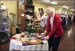 Ruth Arnot, a volunteer in The Giving Store, arranges a holiday display. Everything is free in the store in the basement of Glenwood Lutheran Church beside the Toledo Museum of Art on Monroe Street.