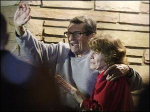 Joe Paterno and his wife, Susan, stand on their porch to thank supporters gathered outside their home.