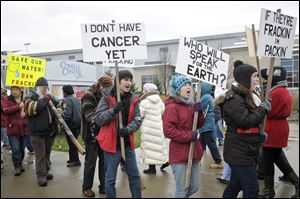 Anti-fracking protestors carry signs while protesting in front of The Covelli Center near downtown Youngstown, Ohio, where the Youngstown Ohio Utica & Natural Gas Conference & Expo took place.