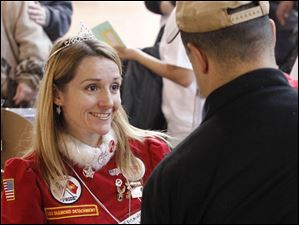 Salvation Army volunteer Kasandra St. Amour of Oregon talks to a customer at the giveaway while wearing a tiara and Mrs. Claus outfit