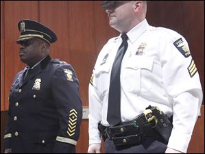 Toledo Police Chief Derrick Diggs stands next to Sgt. Ron Frederick before giving him his new badge during a promotion ceremony in City Council chambers on December 15, 2011.