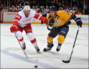 Johan Franzen of the Detroit Red Wings races Shea Weber of the Nashville Predators for the puck.