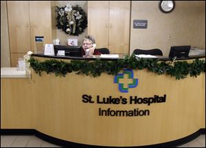 Barb Warner mans the information desk at St. Luke's Hospital, where finances are improving and which is expected to be in the black this year.