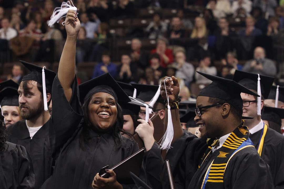 Graduates-Jamillah-Smith-2nd-from-right-and-Derris-Cameron-wave-their-tassels