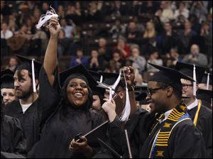 Graduates Jamillah Smith, 2nd from right, and Derris Cameron wave their tassels during the Bowling Green State University's 272nd graduation at The Stroh Center at Bowling Green State University in Bowling Green, Ohio.