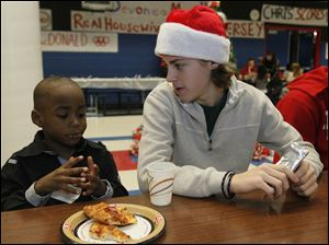 Kimare Huggins, 5, a student at Queen of the Apostles School, left, and St. Francis de Sales High School student Brady Gullette, 18, share a snack before the Christmas party.