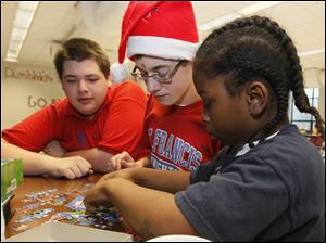 St. Francis de Sales High School students Nick Middleton, 16, and Tommy Cook, 17, put together a puzzle with Caleb Clark, 9, a student at Rosary Cathedral School.