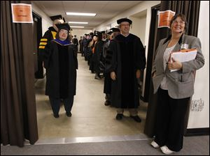 Professors Susana Pena, left, and Federico Chalupa lead the BGSU faculty during the Bowling Green State University's 272nd graduation at The Stroh Center at Bowling Green State University in Bowling Green.