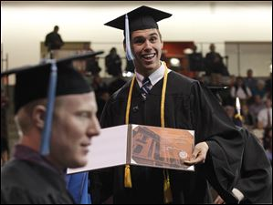 Sylvania resident Nathan Whitman, Cum Laude, shows his diploma to family members in the audience during the Bowling Green State University's 272nd graduation at The Stroh Center at Bowling Green State University in Bowling Green.