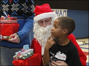 LaMarr Isaac, 7, a student at Queen of the Apostles School, visits with Santa Claus.