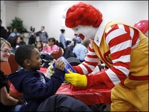 Byron Jackson Jr., 5, helps Ronald McDonald play the accordion during the breakfast.
