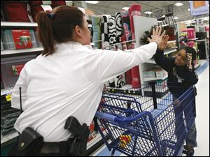 Sgt. Danielle Kasprzak, left, high-fives Avarsheonna Marshall, 11, during their shopping trip to Meijer.