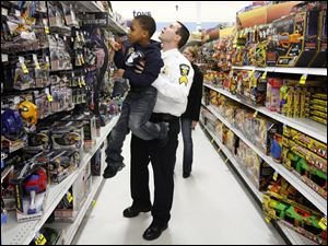 Byron Jackson, Jr., 5, gets a lift from Sgt. Erik Welling as they look for toys at Meijer.
