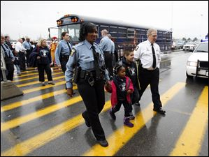 Patrolman Valerie Lewis, left, and Deputy Chief Donald Kenney, right, lead children into Meijer.