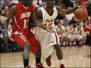 Central player Cliff Bussey, 12, fights off the defense of Lima Senior player Isiah Simpson, 13.