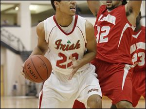 Central player Nathaniel Harris, 22, tries to dribble past Lima Senior player Isiah Stinson, 32.