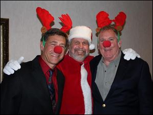 Jeff Stober, Santa Jim Wallace, and Rick Weir get into the seasonal spirit at the Toledo Ski Club's Christmas party.