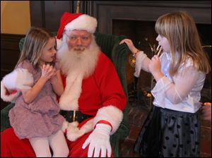 Sarah Stone, 6, left, and Cassie Davis, 6, talk with Santa about their gift wishes.