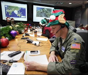 Air Force Lt. Col. David Hanson, of Chicago, takes a phone call from a child in Florida at the Santa Tracking Operations Center at Peterson Air Force Base near Colorado Springs, Colo.