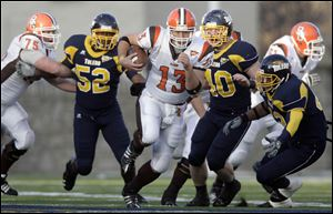 Bowling Green State University quarterback Tyler Sheehan, 13, runs past University of Toledo defenders Johnathan Lamb, 52, Alex Johnson, 40, and Archie Donald, 42.
