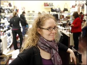 Nicole Firsdon Reza, assistant manager at Clarks shoes, leans against the counter while shoppers fill the store.