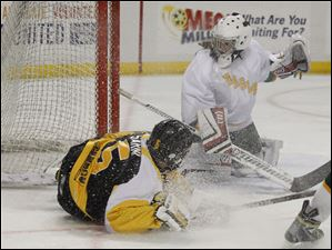 Eagles' netminder Alyssa Batch looks for the puck as Perrysburg's Patrick Sarni meets the ice.