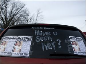 """Have you seen her?"" is written on a van parked at Redline Honda in Fort Wayne, Ind. with flyers for missing 9-year-old Aliahna Lemmon."