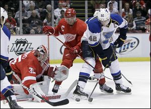 St. Louis Blues center David Backes (42) tries shooting the puck past Detroit Red Wings defenseman Nicklas Lidstrom (5) and goalie Jimmy Howard (35) during the first period of an NHL hockey game in Detroit, Tuesday.