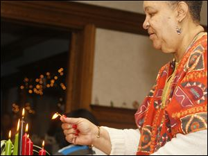 Mistress of Ceremonies Diane Gordon lights the candles on a kinara representing Nguzo Saba, the seven principles of Kwanzaa, during the Kwanzaa program at Padua Center on Tuesday.