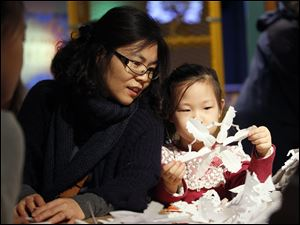 Yunju Seo, left, Bowling Green, admires the snowflake made by her daughter Somin Jin, 6, as they attend a workshop by Dr. Thomas Clark, a retired physician from the University of Michigan, who is know as