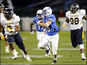Air Force wide receiver Jonathan Warzeka, center, runs away from Toledo safety Diauntae Morrow, left, and Elijah Jones (98).