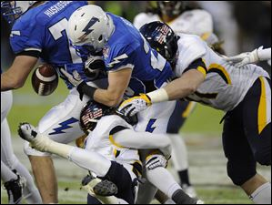 Air Force kick returner Cody Getz, center, fumbles as he is tackled by Toledo defensive lineman Zac Rosenbauer, right.