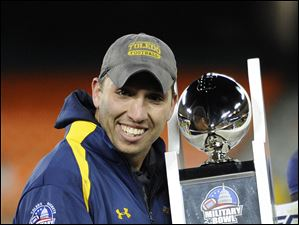 Toledo head coach Matt Campbell holds the trophy after the 42-41 victory over Air Force.